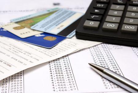 Heap of bills and checks, credit cards, the calculator, a ball pen.
