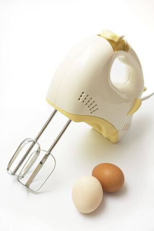 mixer and two eggs on white background