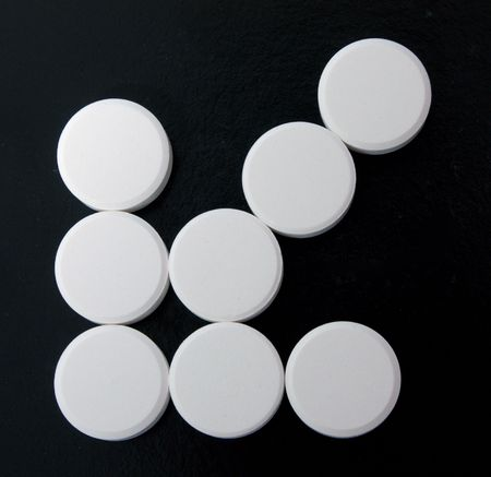 troche: arrow of white tablets on black background. Contept harm from medicines.
