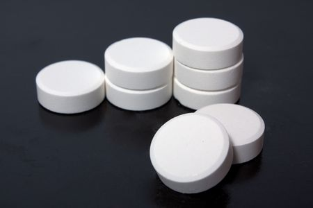 troche: heap of white tablets on black background