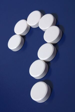 Question mark of white tablets on dark blue background. Stock Photo