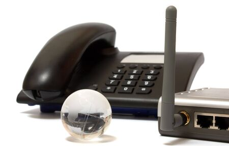 Black office phone, gray wi-fi router and glass globe on white