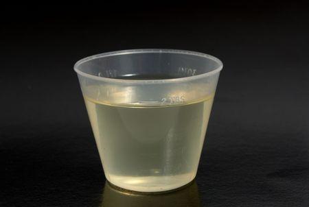 dosaggio: Un dosaggio di medicina freddo giallo � una tazza di misurazione  Archivio Fotografico