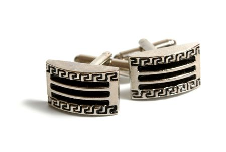 a pair of stainless steel cufflinks on white photo