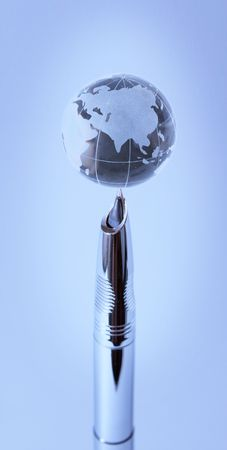 Crystal globe on nib of fountain pen in blue light photo