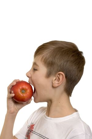 The boy eats an apple isolated on white background