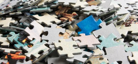 unsolved: the background unsolved bunch of jigsaw puzzles pieces  Stock Photo