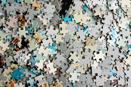 the background unsolved bunch of jigsaw puzzles pieces  Reklamní fotografie