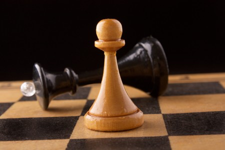black chess queen lays on a chessboard, black background photo
