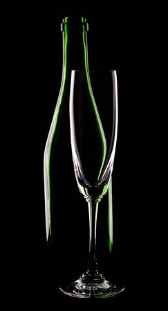 green glass bottle of wine and wineglass on black background photo