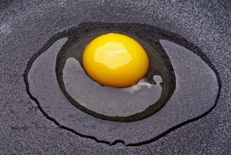 eye catcher: raw egg cracked on a black plate Stock Photo
