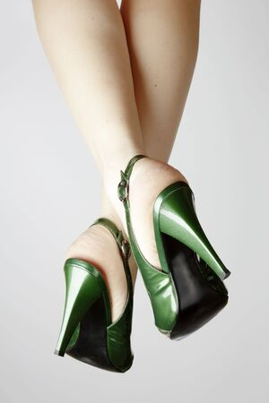 Sexy green leather high heels stilettos shoes and womens legs photo
