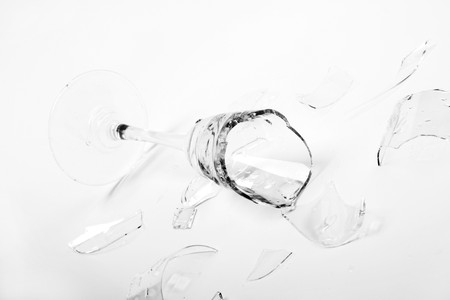 Broken wineglass on the white background. Black and white. photo