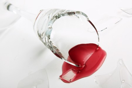 Broken wineglass on the table. Poured red wine, like blood. photo