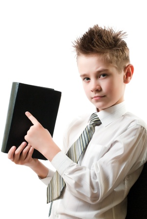 serious boy points his finger at the book isolated on white background photo