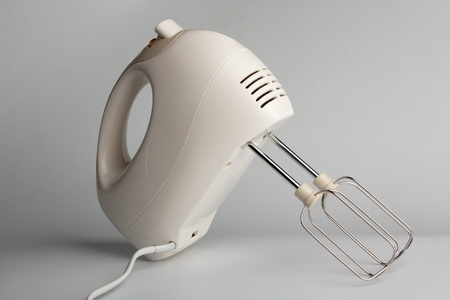 white electric food mixer with beaters on white table photo