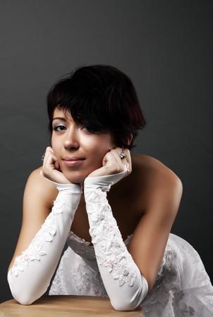 Slim beautiful woman in wedding dress over gray studio background photo