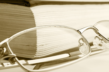 A pair of glassess setting on the book in sepia