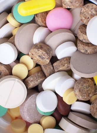 nutritional supplement: the medical background - heap of colored tablets