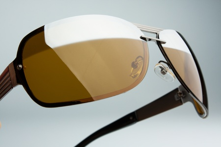 protecting spectacles: A pair of brown sunglasses on a gray background