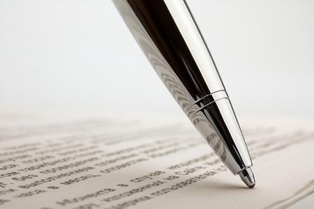 Ballpoint pen on contract. Focus on the reflection of ballpoint pen.