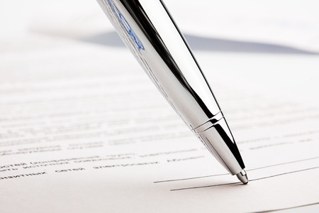 stereotypically: Ballpoint pen on contract. Focus on the reflection of ballpoint pen.