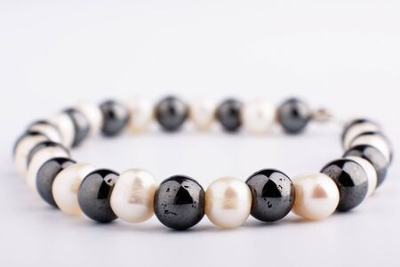 saltwater pearl: White pearls and black stone beads on a thread Stock Photo