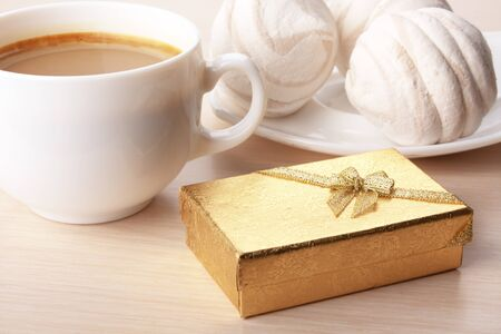The Giftbox And Cup Of Coffee In Wood Surface