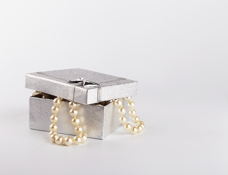 silver gift box with string of pearls on white background photo