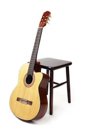 stools: brown wooden stool and a six string guitar Stock Photo