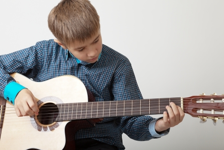 13 year old teenage boy concentrating on playing acoustic guitar.