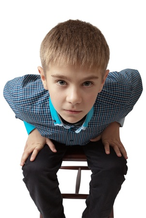 surprised boy sitting on a chair isolated on white photo