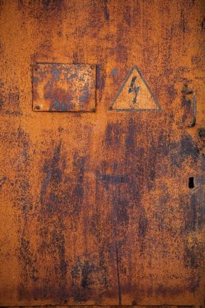 Old rusty metal door with the sign  Danger High Voltage