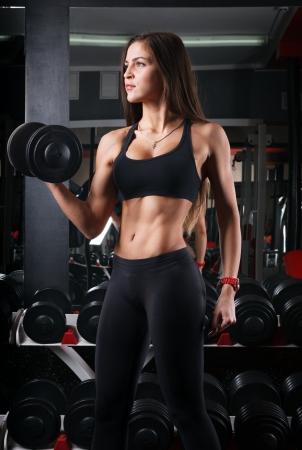 아령을 들고 체육관에서 여자 선수