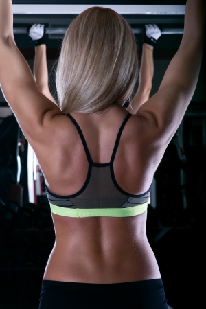 back muscles: woman athlete at the gym holds a post back view Stock Photo