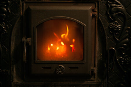 fire burning in the fireplace behind a glass door photo