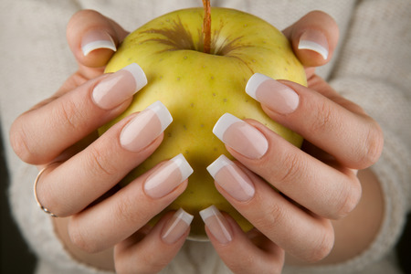 female hand with manicured nails holding an apple photo