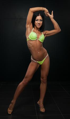 beautiful young woman in a green bikini on a dark background photo