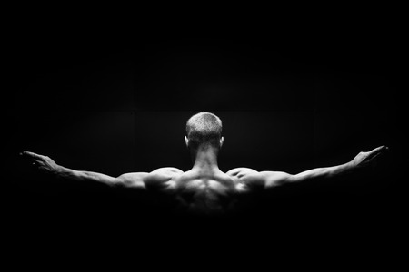 the muscular mans back  on black background photo
