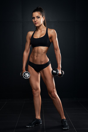 sporty woman on dark with dumbbells