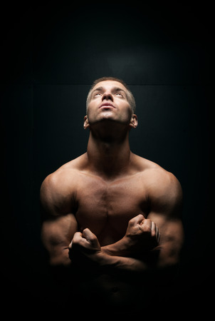 young handsome sexy man looking up on a dark  Stock Photo