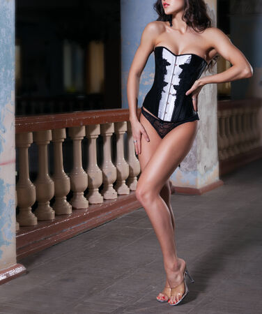beautiful sexy woman in corset in an abandoned house photo