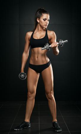 levantando pesas: Mujer deportiva en el fondo oscuro con pesas Foto de archivo