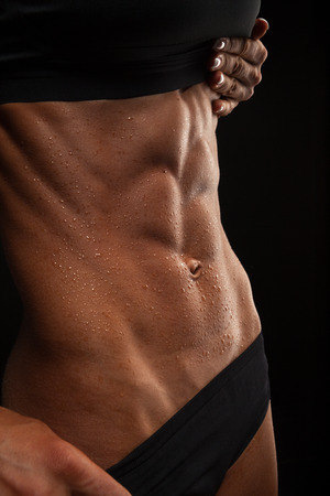 Beautiful athletic woman shakes her abdominal muscles on dark background