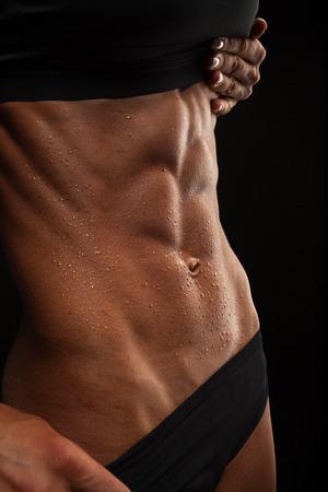 Mooie atletische vrouw schudt haar buikspieren op een donkere achtergrond
