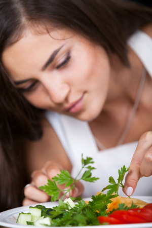 beautiful young girl preparing a salad of fresh vegetables photo