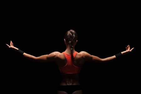 'fit body': Athletic young woman showing muscles of the back and hands on a isolated black background