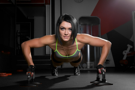 push people: Beautiful athletic woman is pushed up on  a dark background Stock Photo