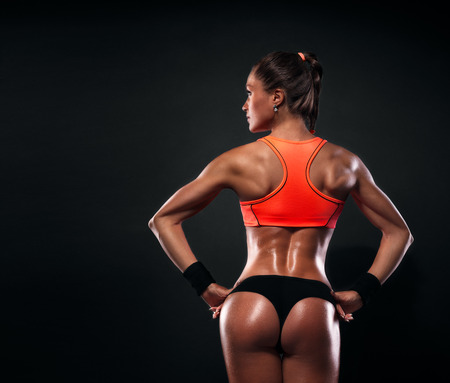 women exercise: Athletic young woman showing muscles of the back and hands on a isolated black background