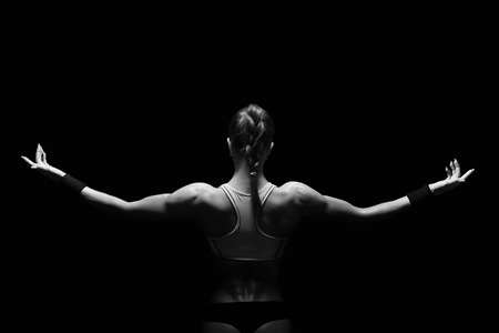 female bodybuilder: Athletic young woman showing muscles of the back and hands on a isolated black background